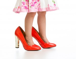 Little girl in big mommy shoes